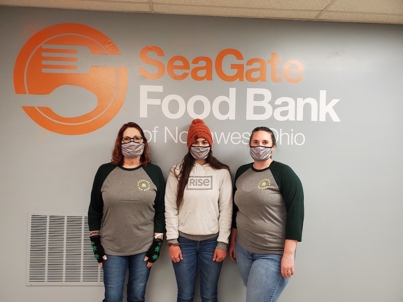 Three women standing in front of the SeaGate Food Bank logo